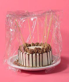 Protect the icing on cakes by inserting a few sticks of uncooked spaghetti in the surface of the cake before wrapping in plastic to prevent the covering from messing up your decorating job.