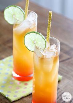 3 ounces of pineapple juice 2 ounces of orange juice 1 ounce dark rum, plus 1/2 ounce to splash on top 1 ounce coconut rum splash of grenadine lime slice for garnish
