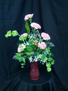 This arrangement was done in a pink half dozen rose vase. It has 6 carnations, 1 bupleurum, 1 limonium, 3 bells of ireland, 1 gyp, 2 hypericum, myrtle, salal, and leather.