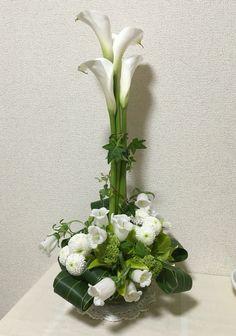 4月のアレンジ。2部構成、パラレルと升。カラーの刺し方は、ためらわずに真っ直ぐ深く。アイビーでまとめて安定させる。 升の構成は、カラーの支柱のバックも含めて全体で考える。 Flower Arrangements, Glass Vase, Flowers, Plants, Home Decor, Floral Arrangements, Decoration Home, Room Decor, Plant