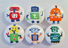 Robot Dresser Knobs hand painted on a white background with red, orange, lime green, navy blue, yellow and light blue robots.   Find them at the Little Nursery for $6.50 each