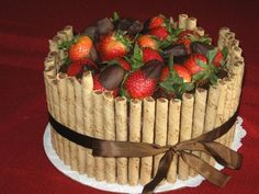 Chocolate cake with chocolate frosting. Strawberries dipped in chocolate with pirouettes