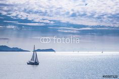 Sailing boat on blue sea waters with clear blue sky