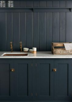 Navy kitchen features navy shaker cabinets adorned with brass vintage latch hardware paired with a white marble countertop fitted with a copper sink and copper faucets and a navy beadboard backsplash with shelf.