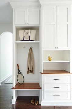 Beautiful mudroom features built-in cabinets fitted with a built-in bench with overhead shelf next to a built-in desk.