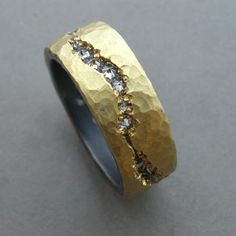 Todd Pownell: , Ring in 18k yellow gold over oxidized sterling silver, with inverse set diamonds set in an irregular river-like channel around ring. Measures 7mm wide. (May be ordered to size, allow 3-4 weeks). Each ring is handmade and unique. Slight variations occur