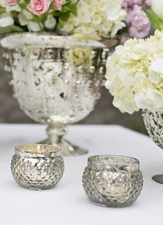 Mercury glass compotes surrounded by mercury glass votives.