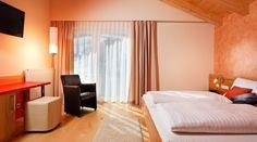 Zimmer im Hotel Auwirt - Unsere 47 Zimmer begrüßen in alpenländischer Tradition mit Holzböden und Mansarden, stilvoll und schlicht. In Betten von ausgezeichneter Qualität wird Ihr Schlaf tief und erholsam sein. Warmes Sonnenlicht begrüßt Sie nicht nur durch unsere Fenster, sondern auch auf Ihrem Balkon. Modern, Curtains, Home Decor, Mansard Roof, Sunlight, Beds, Sleep, Windows, Balconies