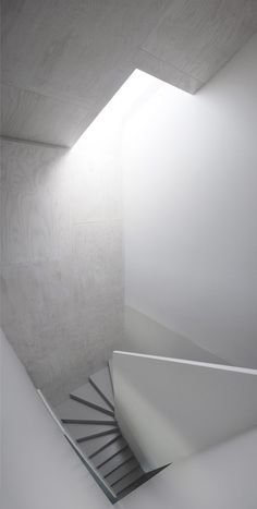 Light pouring dorn in the staircase by X Architekten.