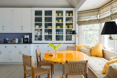 Blue and white kitchen, tangerine accents and French rope chairs