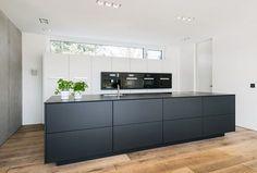 Die Küche in schwarz weiß harmoniert perfekt mit dem Eichenparkett und der Wand aus Sichtbeton