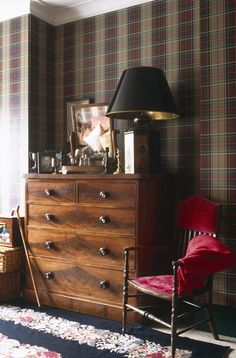 Decorating With Plaid: For a traditional-meets-eclectic feel, pair a classic tartan wall covering with a rug in a contrasting pattern, and layer in warm-wood and metallic accents.