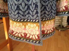 Vidunderlig jakke. Strikket af 100 % uld.  Blomsterranke og bladmønster er kopieret fra den norske designer Solvej Hisdal.  Selve design og mønster er mit eget.  Der er belægninger inde i ærmekant, nederst på jakken og langs forstykkerne. Det giver en god facon og et elegant snit.