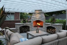 mid sized classic backyard patio design with a fire feature a pergola and natural stone pavers rattan framed sofa with beige color of Outdoor Corner Fireplace, a Great Warm Spot Outside Your House