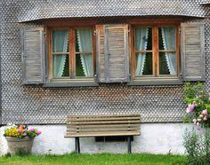 ein typisches Bregenzerwälderhaus. Der Stolz der Hausfrau sind die selbst gehäkelten Spitzen am Vorhang