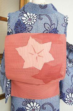 スモークがかった、ほのかにベージュみをおびたニュアンス感のある優しいピンク色の濃淡で織り出された星のような葉模様が絵本のように愛らしい絽の夏の開き名古屋帯です。