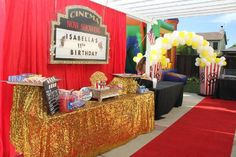 Movie Night Theme birthday party, dessert table, popcorn cake, concession stand, glitzy linen, popcorn arch, movie sign, red carpet, event design, idea, candy, hot dogs, movie screen, candy table