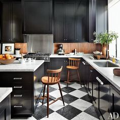 A walnut backsplash and vintage George Nakashima barstools warm the kitchen, which is outfitted with black cabinetry and marble flooring | archdigest.com