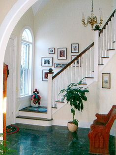 New double doors were installed between two round-arched windows to create a two-story entry foyer with stairs to the upper level. The banisters, posts, and finials were created on-site by James and his family in his basement woodworking shop. The arched opening connecting the entry to the living room is a new feature but repeats the arch of the windows. Verde marble provides a durable yet elegant surface for the entry floor.