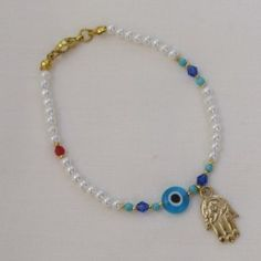 "$6.65 Charming enough to ward off the evil eye! This elegant faux pearl bracelet makes a great fashion accessory with a beautiful interplay of ivory hued faux pearls and blue & red crystal beads. The gold Hamsa dangles from the bracelet, while the gold clasp adds sparkle to the bracelet. This evil eye bracelet with a fashion twist makes a great gift for those whom you hold dear.  Bracelet measures 7.5""."