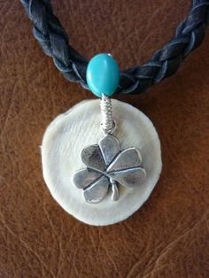 Hunter necklace, hand braided deerskin, antler slice, sterling silver wire and lucky charm accented with turquoise. $55