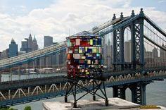 Stained Glass Watertower Sparkles Along Brooklyn's Skyline   Born in L.A. and now based in New York, artist Tom Fruin created a recent installation that adds a little sparkle to the already dazzling Brooklyn skyline. His monumental sculpture, Watertower, is built out of salvaged plexiglass and steel, and is mounted high upon a water tower platform located in DUMBO, Brooklyn.  