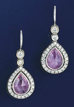 A pair of pink sapphire and diamond earpendants  Each pear shaped fancy-cut pink sapphire to brilliant-cut diamond surround and graduated two stone collet surmount, hook fittings