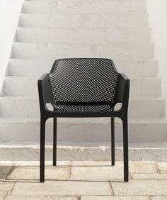 Made of a fiber glass resin monocoque, this modern, outdoor chair is painstakingly punched with a mesh-like pattern of square and round slots.