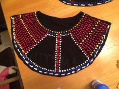 This is the beginning of our Rafiki costumes for Lion King kids. I cut the collars out of old black t-shirts turned inside out. Then I used puffy paint to make it look beaded. Next I'll add feathers.