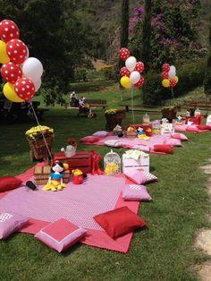 Idee für eine Gartenparty: Bunte Decken und farblich passende Kissen auslegen - mehrere Stationen. Dazu Ballons und Blumen zur Deko.