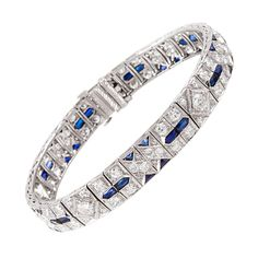 Art Deco Sapphire Diamond Bracelet. Iconic art deco styling, offering a symbiotic combination of geometrics in diamonds with sapphire accents. Rendered in platinum, with approximately 7 carats of brilliant white diamonds. 7 inches in overall length and 3/8 of an inch wide. c 1930