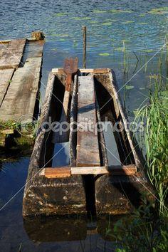 vieux bateau de pêche traditionnel à un quai, les reflets dans l'eau, Russie