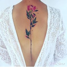 There's something so beautiful about spine tattoos to me. I love this simple floral design that uses soft colors. I thought it was interesting to see a flower in the center, rather than a quote or lotus that's commonly popular with spine tattoos.