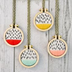 "This hand-stitched pendant combines a simple, classic pattern with a bold pop of color. The perfect statement piece!Miniature wooden hoop measures 1.6"". Antique Brass chain measures 27.5"" in total length. Features abstract pattern seed stitched on natural speckled cotton.Available in RED, MINT, YELLOW, and PEACH. Have another color in mind"