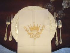 Set a gorgeous table with these lovely Crown Dinner Napkins. Standard dinner napkin/guest towel size. White cotton/linen blend embroidered with a golden crown design. Cold water wash, iron on reverse side. Perfect as a Queen hostess gift too! Choose A. Black with Gold Crown ,