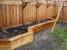 Raised planter box along fence that doubles as a bench. Also brackets for hanging plants