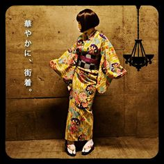 kimononagoya: This is a Taisho-era inspired yukata with the typical festive furisode-style floral print, yabane (feather) background with large flowers, and geometric obi that are tags of the Taisho (~1930s) kimono fashion. The obijime is possibly an obiage, worn folded as a thick ribbon, though you can also use a belt for this.