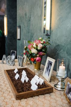 Angela and Wynston's mother made the escort card display together. It was constructed of wood and filled with fresh, fragrant coffee beans. #creativeplacecardtable Photography: Sarah & Ben. Read More: http://www.insideweddings.com/weddings/florida-wedding-celebration-with-vibrant-colors-and-wooden-details/644/