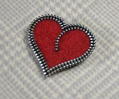 This red heart zipper brooch is made from a red sweater I found at the thrift store and then shrunk down (felted) via multiple washings. I then cut the heart I designed out and surround it with zipper! The silver zipper adds a bit of bling and complements the matte texture of the wool