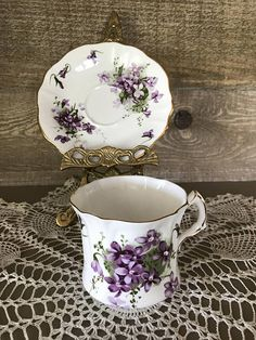 Vintage Hammersley Victorian Violets from Englands Countryside Made in England Bone China Tea Cup and Saucer. This beautiful tea cup and saucer is not lacking in detail with purple violets on both cup and saucer as well as gold trim there are also some raised ruffle design on both pieces.