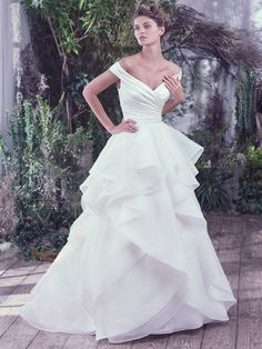 Asymmetrically pleated L'Amour satin creates a refined fitted bodice before flaring into a sculptured Venice organza ball gown skirt featuring horsehair edged layers. Off-the-shoulder sleeves create a portrait neckline flaunting an exquisitely romantic style. Finished with covered buttons over zipper closure.  All Diamond White (pictured) Available in Sizes 0-28    Your browser does not support the video tag.