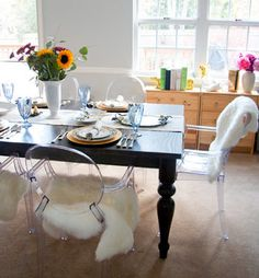 IKEA faux sheepskin rugs on Ghost chairs in dining room