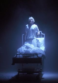 A man stands on a hospital bed in his pajamas illuminated by a divine light. Headlong's Angels in America - stupendous