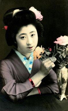 Geiko Momotaro with a vase of roses, 1920s