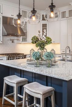 Gorgeous kitchen with white cabinets, glass globe pendants and navy island!