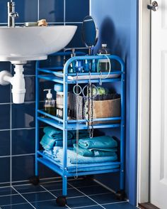 Blue cart standing next to sink; IKEA cart, for extra storage with pedastol sink