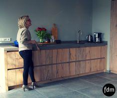 Deze landelijke greeploze keuken is geheel op maat gemaakt van oud balk eiken. Het betonnen aanrechtblad en de inductiekookplaat van Bora geven het geheel een moderne twist.