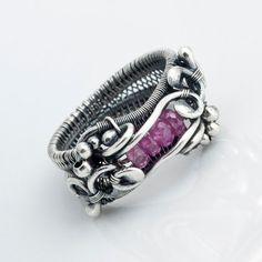Fine silver wire has been woven and sculpted into this beautiful filigree ring. Nestled in the ring are 4 faceted Raspberry pink Sapphires. The ring is a size 7. If you would like this ring in another size, or with a gem of your choice send me an email. I would be happy to work with you to create a ring just for you.