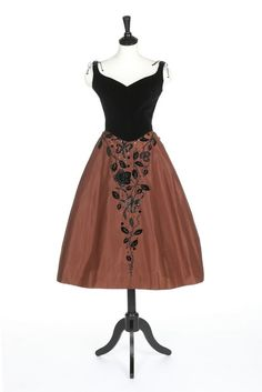 A Charles James for Samuel Winston black velvet and chestnut taffeta cocktail dress, mid 1950s. labelled and also with hand written tape 'Brodericle', the separate velvet bodice with sweetheart neckline, laced thongs at the shoulders; the stiffened skirt embroidered, beaded, sequined and appliquéd with rose trails and bows,