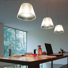A row of FLOS Romeo Moon pendant lamps add a bright glow to this dining space with a wood table and large windows.